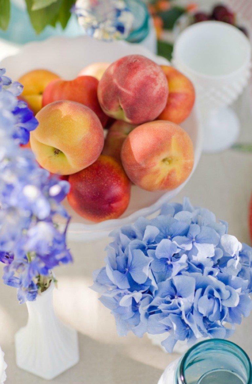Sommerliche Gartendekoration für ein Fest im Freien mit frischen Erdbeeren, Kirschen und Pfirsisch